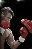 Uppercut. Low key portrait of boxer getting ready for fight Royalty Free Stock Photography