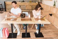 uppfostrar genom att använda grejer, medan deras son borrade i kafé Arkivbilder