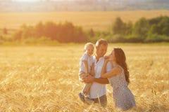 Uppfostrar lycka som går på fältet med barnet arkivbild