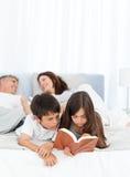 Uppfostrar samtal, medan deras barn läser Royaltyfri Bild