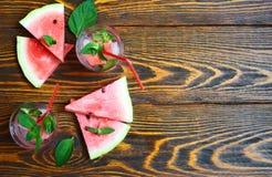 Uppfriskande coctail för sommar av vattenmelon, den gröna mintkaramellen och isvatten på en träbakgrund i ett exponeringsglas med Arkivbild