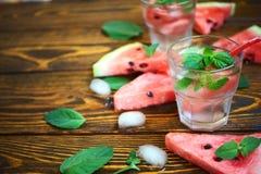 Uppfriskande coctail för sommar av vattenmelon, den gröna mintkaramellen och isvatten på en träbakgrund i ett exponeringsglas med Royaltyfria Bilder