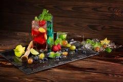 Uppfriskande coctailar med limefrukt, is, bär, mintkaramellen och carambolaen på träbakgrunden Sommardrycker kopiera avstånd Royaltyfri Fotografi