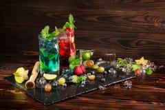 Uppfriskande coctailar med mintkaramellen, limefrukt, is, bär och carambolaen på det svarta skrivbordet Färgrika sommardrycker ko Royaltyfri Bild
