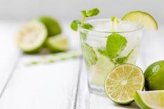 Uppfriskande coctailmojito för sommar med limefrukt och mintkaramellen på vit trätappningbakgrund royaltyfri foto