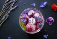 Uppfriskande drink med ätliga blommor royaltyfri fotografi
