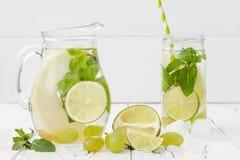 Uppfriskande hemlagad limefrukt- och mintkaramellcoctail över trätabellen för gammal tappning Ingett smaksatt vatten för Detox fr Royaltyfri Fotografi