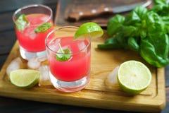 Uppfriskande kall jordgubbecoctail med limefruktskivor och basilika s Arkivfoto