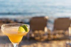 Uppfriskande klassiska Margarita Cocktail With Lime And som är salt vid stranden på solnedgången på suddig bakgrund Royaltyfria Bilder