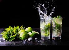 Uppfriskande lemonad för sommarcoctailmojito med färgstänk Particoctail Limefrukt, is och mintkaramell på tabellen _ arkivbild