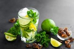 Uppfriskande mintkaramellcoctailmojito med rom och limefrukt, kall drink eller dryck med is på svart bakgrund arkivfoton