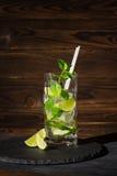 Uppfriskande mojitococtail med mintkaramellen, iskuber och skivor av limefrukt i ett highballexponeringsglas på träbakgrunden kop Arkivbilder