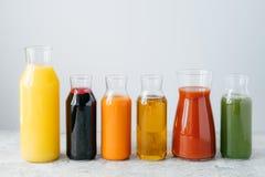 Uppfriskande sommardrinkar Apelsin-, morot-, äpple-, tomat-, spenat- och granatäpplefruktsaft i exponeringsglaskrus som isoleras  arkivbild