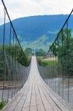 Upphängningbro över bergfloden arkivbild