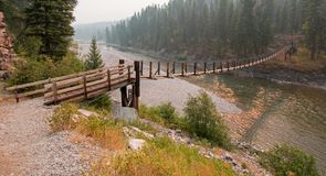 Upphängningbro över den Flathead floden på den prickiga björnkommandosoldatstationen/tältplatsen i Montana USA Fotografering för Bildbyråer