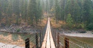 Upphängningbro över den Flathead floden på den prickiga björnkommandosoldatstationen/tältplatsen i Montana USA Royaltyfri Foto
