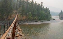 Upphängningbro över den Flathead floden på den prickiga björnkommandosoldatstationen/tältplatsen i Montana USA Royaltyfri Bild