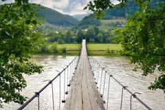 Upphängningträbro över floden i bergen vid en sommardag Arkivbilder