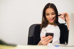Upphetsad affärskvinna som segrar efter sammanträde för telefon för prestationläsning smart i ett skrivbord på kontoret Royaltyfri Foto
