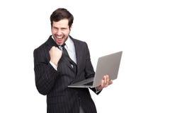 Upphetsad affärsman med en bärbar dator arkivbilder