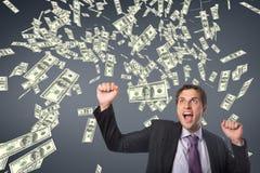 Upphetsad affärsman med pengarregn mot blå bakgrund royaltyfri fotografi