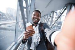 Upphetsad affärsmanTaking Selfie In flygplats som rymmer passet arkivbild