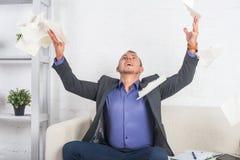 Upphetsad affärsman som kastar legitimationshandlingar på kontoret Royaltyfri Fotografi