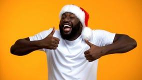 Upphetsad afrikansk amerikanjultomtenman som visar upp tummar, ferier f?r lycklig jul fotografering för bildbyråer