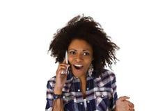 Upphetsad afrikansk amerikankvinna med mobiltelefonen Arkivbild