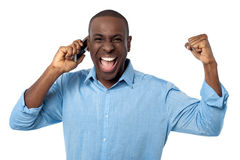 Upphetsad afrikansk man som talar på mobiltelefonen Fotografering för Bildbyråer