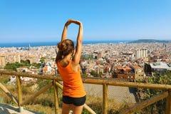 Upphetsad attraktiv ung kvinna i sportswearen som sträcker tycka om det Barcelona landskapet i morgonen Arkivfoton