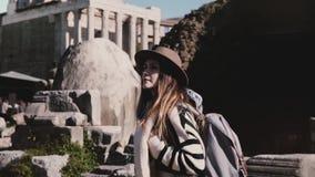 Upphetsad attraktiv ung kvinnlig turist med ryggsäcken i stilfull hatt som undersöker forumet i Rome som ser runt om att le stock video