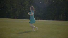 Upphetsad barfota flickaspring längs grönt fält arkivfilmer
