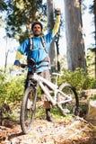 Upphetsad bergcyklist i skog Fotografering för Bildbyråer