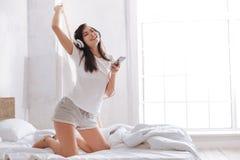 Upphetsad brunett som lyssnar till musik på säng arkivbild