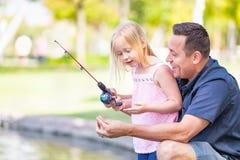 Upphetsad Caucasian fader och dotter som har roligt fiske på laen arkivfoto