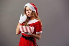 Upphetsad charmig mrs Iklädda Claus den röda ämbetsdräkten, jultomten hatt och vita handskar rymmer julgåvan i hennes händer arkivfoto