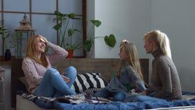 Upphetsad familj som spelar gissning som spelar på sängen lager videofilmer