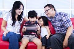 Upphetsad familj som spelar leken på lägenheten Arkivbild