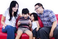 Upphetsad familj som spelar leken på den isolerade internet - Royaltyfri Bild