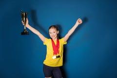 Upphetsad flicka med medaljer och trofékoppen Royaltyfria Bilder