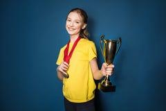 Upphetsad flicka med medaljer och trofékoppen Royaltyfri Fotografi