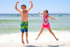 Upphetsad flicka och pojke som tillsammans hoppar på stranden Royaltyfri Bild