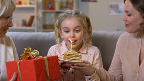 Upphetsad flicka som blåser födelsedagstearinljuset som extremt är lycklig att fira med familjen lager videofilmer