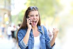 Upphetsad flicka som har en telefonkonversation i gatan arkivfoton
