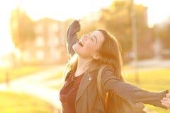 Upphetsad flicka som lyfter armar i gatan royaltyfri foto