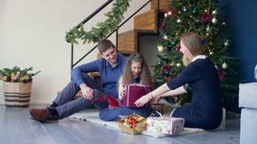 Upphetsad flicka som mottar julgåvan från föräldrar stock video