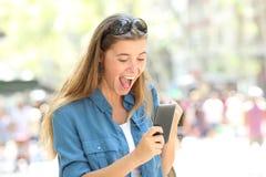 Upphetsad flicka som rymmer en smart telefon i gatan arkivbild
