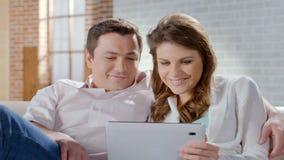 Upphetsad fru och make som ser minnestavlan som direktanslutet shoppar, familjeföretag royaltyfri bild