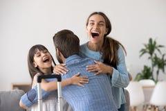 Upphetsad fru och unge som kramar fadern som ankommer efter lång tur arkivbild